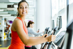 Young fit woman using an elliptic trainer. In a fitness center and smiling Royalty Free Stock Image