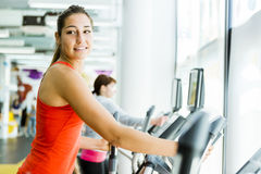 Young fit woman using an elliptic trainer. In a fitness center and smiling Stock Photography