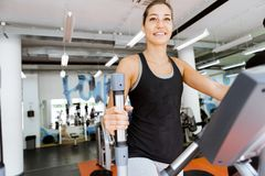 Young fit woman using an elliptic trainer. In a fitness center and smiling Royalty Free Stock Photography