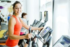 Young fit woman using an elliptic trainer. In a fitness center and smiling Royalty Free Stock Photos