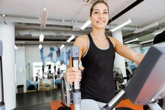 Young fit woman using an elliptic trainer. In a fitness center and smiling Stock Images