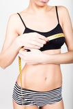 Young fit woman wearing black bra and panties, holding measuring tape with her hands on chest, isolated a white. Background Stock Photos