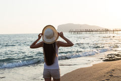 Young fit woman wearing straw hat by seaside stock photo