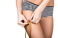 Young fit woman wearing striped panties, holding measuring tape with her hands on thigh, isolated a white background Royalty Free Stock Photos