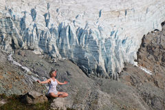 Young Fit Woman in Yoga Pose Meditating in Mountains. Stock Photos