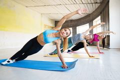 Young fit women doing side plank in gym royalty free stock photo