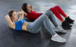 Young fit women at the gym doing abs workout royalty free stock photos