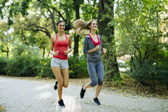 Young fit women jogging outdoors Stock Image