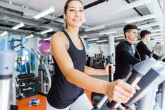 Young fit woman using an elliptic trainer. Young fit women using an elliptic trainer in a fitness center and smiling Stock Images