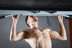 Young fitnaess man doing push up exercise on the horizontal bar at gym. Young fitnaess man doing push up exercise on the horizontal bar at gym Stock Photography