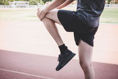 Young fitness athlete man running on road track, exercise workout wellness and runner stretching legs before run concept.  stock image