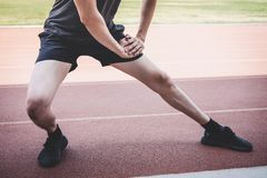 Young fitness athlete man running on road track, exercise workout wellness and runner stretching legs before run concept.  stock photo