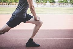 Young fitness athlete man running on road track, exercise workout wellness and runner stretching legs before run concept.  royalty free stock photo