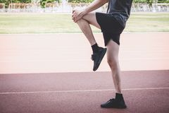 Young fitness athlete man running on road track, exercise workout wellness and runner stretching legs before run concept royalty free stock photos