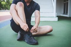 Young fitness athlete man running on road track, exercise workout wellness and runner tying shoelaces with copy space before run.  stock photography
