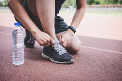 Young fitness athlete man running on road track, exercise workout wellness and runner tying shoelaces with copy space before run.  royalty free stock photo
