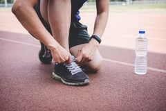 Young fitness athlete man running on road track, exercise workout wellness and runner tying shoelaces with copy space before run.  royalty free stock images