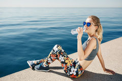 Young fitness blonde woman drinking water after running at beach Royalty Free Stock Photos