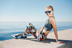 Young fitness blonde woman hold bottle water after fit at beach Stock Photo