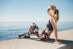 Young fitness blonde woman hold bottle water after fit at beach. Royalty Free Stock Images