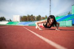 Young fitness brunette woman runner push up on stadium track. Young fitness woman runner push up on stadium track stock photography