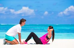 Young fitness couple doing side crunches on white Royalty Free Stock Photography