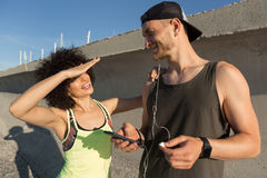 Young fitness couple listening to music with earphones outdoors Royalty Free Stock Image