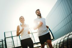 Young fitness couple running in urban area. Young fitness couple running together in urban area stock photo