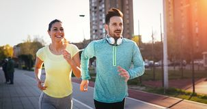 Young fitness couple running in urban area. Young fitness couple running together in urban area royalty free stock photos