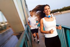 Young fitness couple running in urban area royalty free stock image