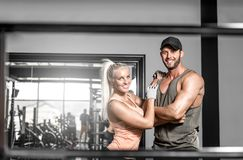 Nice fitness couple in gym. Young fitness couple in 20s standing together in modern fitness center and showing their perfect body. Toned image stock image