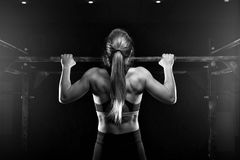 Young fitness female doing pull ups exercise. Young muscular woman doing pull up exercise on horizontal bar. Fit female practicing strength training. Fitness Royalty Free Stock Photography