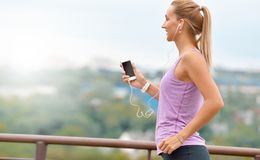 Young fitness female joger is runing and listening to music during the run royalty free stock photos