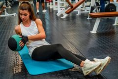 Young fitness girl does abs exercises with a ball in gym. View of attractive fit girl exercising with ball on floor of modern gym royalty free stock images