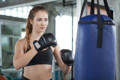 Young fitness girl doing exercise hitting punching bag at a boxing studio gym.woman boxer in sportswear working out with gloves. Beautiful, health, thai, white stock images