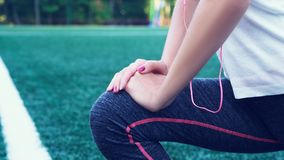 Young fitness girl doing stretching on the stadium. Summer sport activity. Green stadium grass on background. Young fitness girl doing stretching on the stadium royalty free stock photography