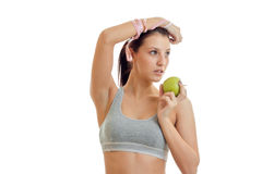 Young fitness girl grey top raised her hand up and keeps the Green Apple close-up Stock Photo