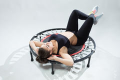 Young fitness-girl make exercises on rebounder Stock Image