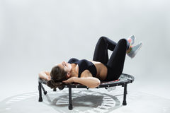 Young fitness-girl make exercises on rebounder Stock Images