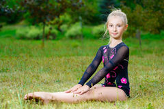 Young fitness girl sitting in park on green grass Stock Images