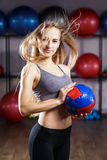 Young fitness girl standing with medicine ball. Young fitness blonde girl standing with medicine ball in fitness center Royalty Free Stock Photography