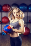 Young fitness girl standing with medicine ball. Young fitness blonde girl standing with medicine ball in fitness center. Warm color toned image Stock Photo