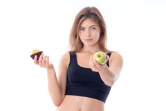 Young fitness girl stretches forth his hand with an Apple and a second  keeps the fruitcake Stock Photos
