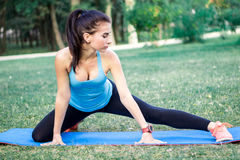 Young fitness girl stretches legs for training workout. Young fitness girl stretches for training workout outdoor Stock Photo