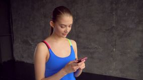 Young fitness girl using a mobile phone after fitness. Close-up of a girl in the gym with a phone. Portrait of a happy. Young fitness girl using a mobile phone stock video