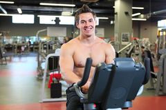 Young fitness guy working out on exercise bike Stock Image