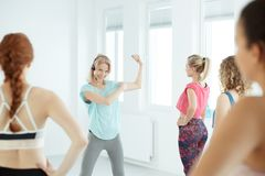 Young fitness instructor. Explaining an exercise for a group royalty free stock images