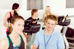 Young fitness instructor people exercise at gym stock photo