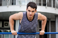 Young fitness man exercises on horizontal bar during training wo Royalty Free Stock Images