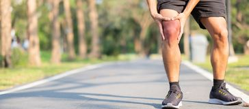 Young fitness man holding his sports leg injury. muscle painful during training. Asian runner having knee ache and problem after. Running and exercise outside stock photo